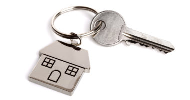 Silver house shaped keychain and key isolated on white