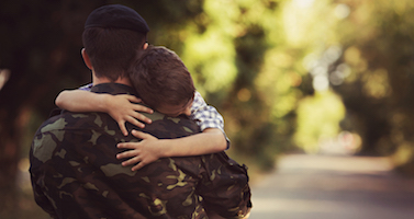 Little boy and soldier in a military uniform say goodbye before a separation